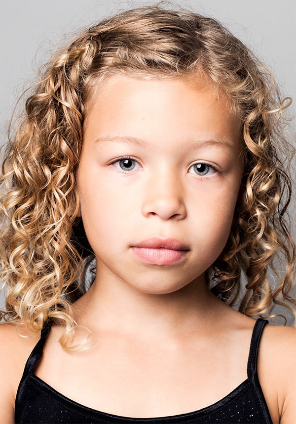 Color portrait of female child model Autumn Massey goldie locks golden hair with curls looking into camera wearing a black strap top mixed race child photographed by danish Brooklyn based photographer Maria Bruun