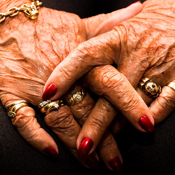 Color photograph of old female hands folded together her hands are wrinkled showing her blue veins she is wearing gold rings a gold bracelet and red nail polish black background photographed by danish Brooklyn based photographer Maria Bruun