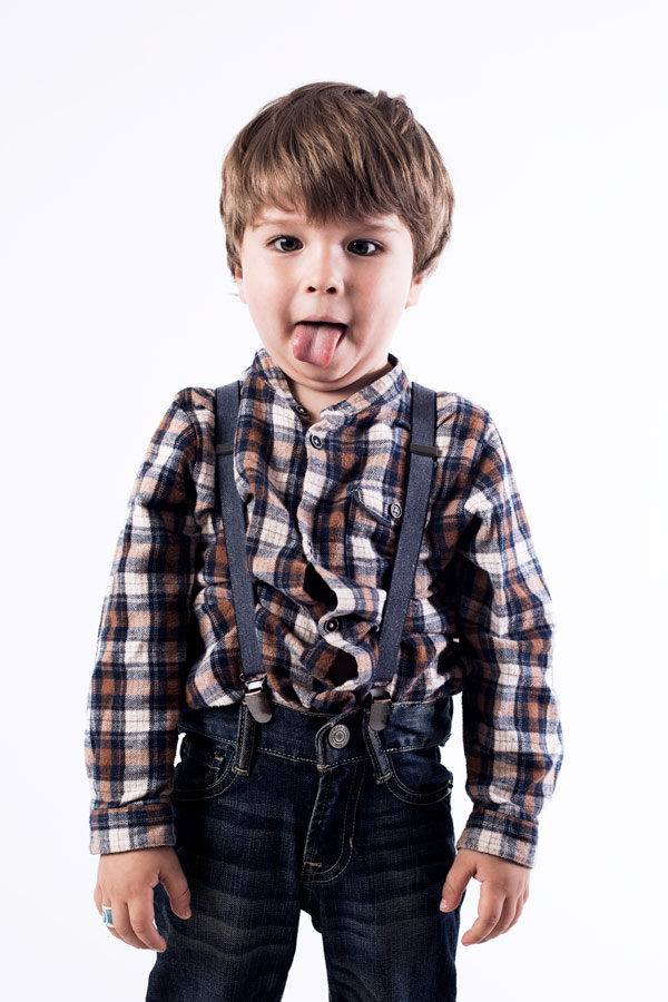 Color portrait of male child model Gabo 3 years old he is wearing Gab Kids denim suspenders a hipster shirt child hipster he is sticking his tongue out playing white background studio light setup shot on canon 5D camera photographed by danish Brooklyn based photographer Maria Bruun