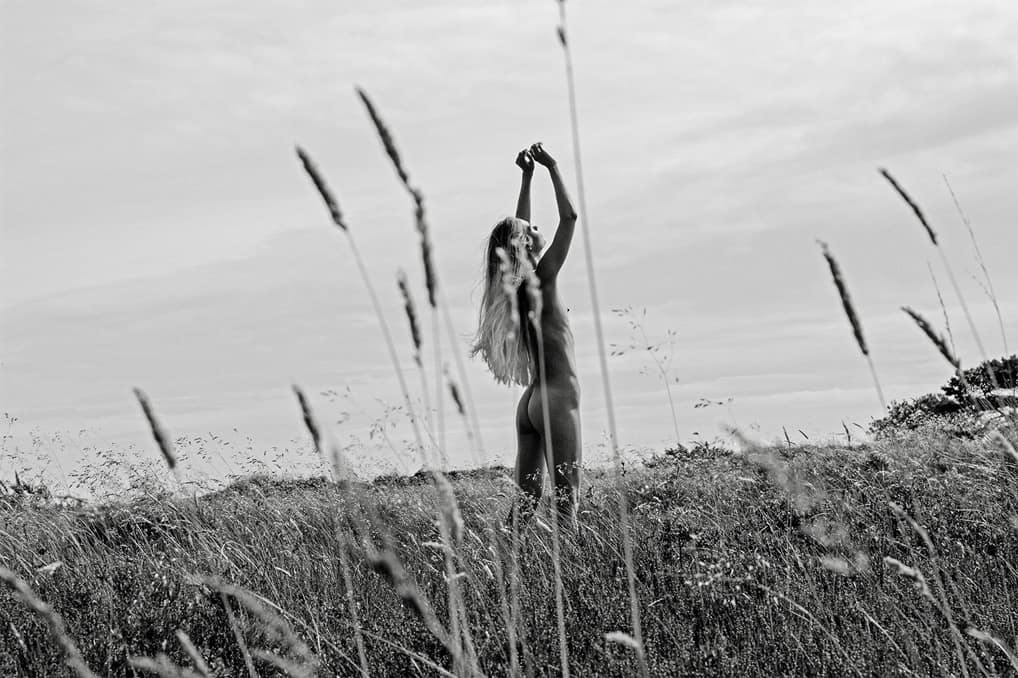 Black and white portrait of female danish model Mona Stilling she is standing naked in a field in Denmark her arms are lifted to the sky the summer sun shinning on her her butt is showing the corn in the foreground photographer Maria Bruun