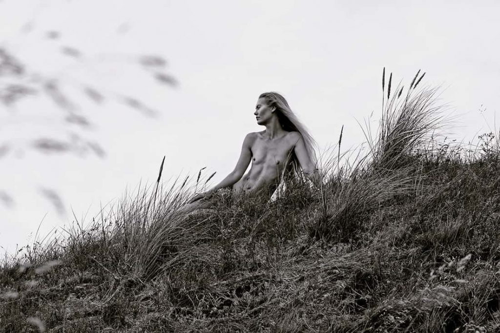 black and white portrait of female danish model Mona Stilling she is sitting naked in a field in Denmark looking of to the side she has high cheekbones and her abs are showing photographer Maria Bruun