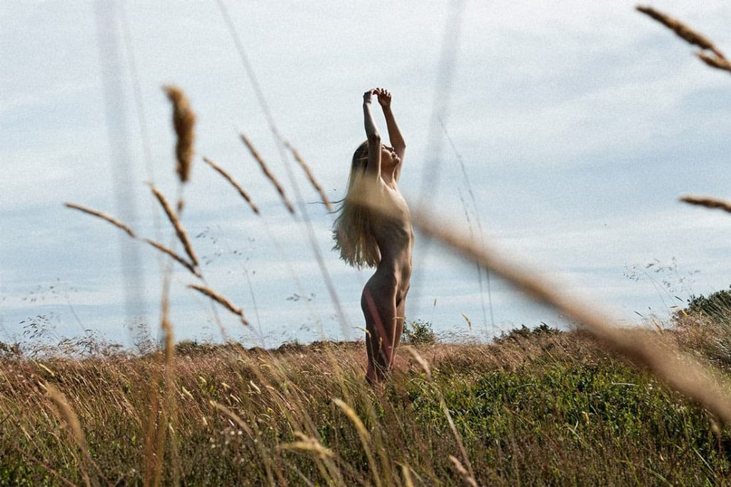 Color portrait of female danish model Mona Stilling she is standing naked in a field in Denmark her arms are lifted the summer sun shinning on her photographer Maria Bruun