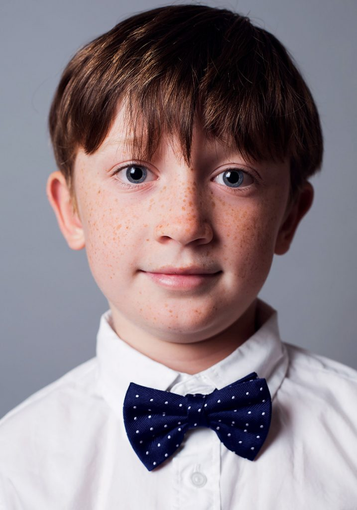 Color portrait of male child model Phillip he has freckles he is smiling wearing a blue bowtie and white shirt he is looking into camera he has bright blue eyes photographed by danish Brooklyn based photographer Maria Bruun