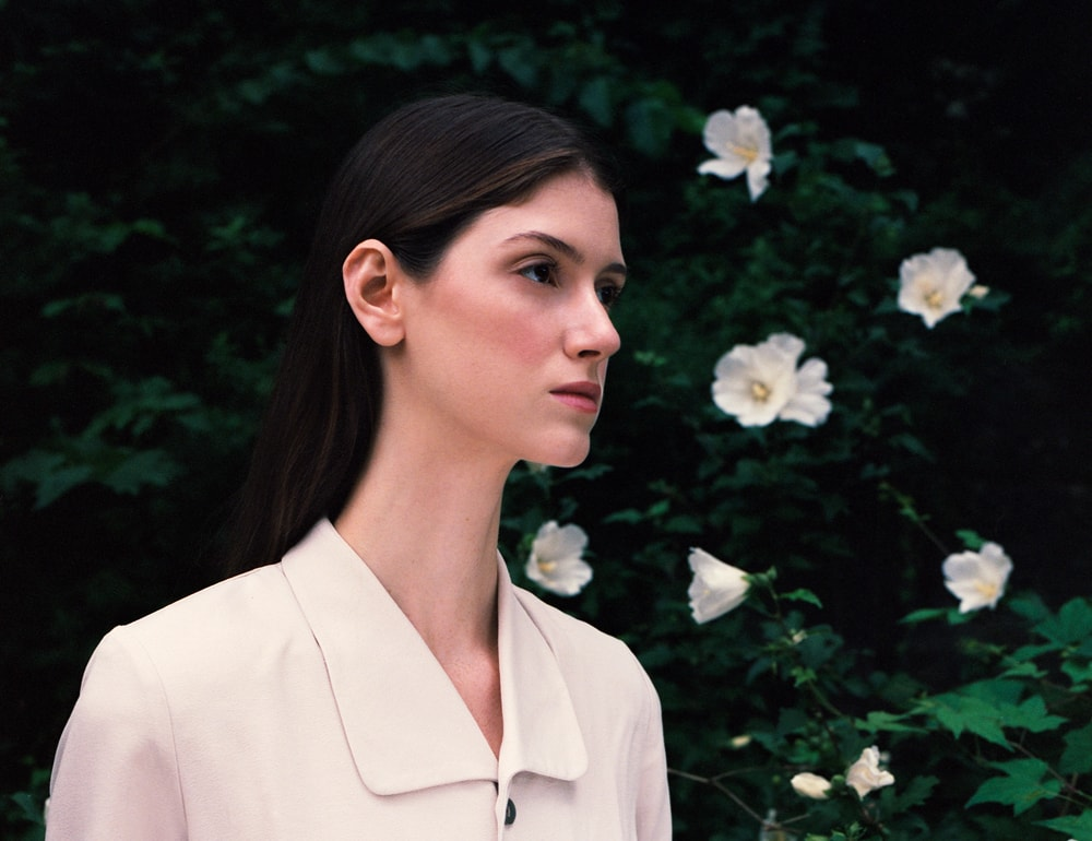 Model Shay Davis, Photographer Maria Bruun, central park, photo captured model from profile, brown hair, high cheekbones, flowers in the background, flowers in picture, trees, medium format photography, medium format analog photography, medium format film fine art photography, medium and large format photography, medium vs large format photography, medium format fashion photography medium format photography blog, medium format photography, photographer to hire, photographer to hire near me, photographer to follow on instagram, photographer for hire, photographer for hire New York, photographer with camera, photographer near me for photoshoot, photographer or photography, photographer or videographer, photographer or artist, photographer or photograph, photographer or photographer, photographer or filmmaker, photographer or cinematographer, photographer and videographer package